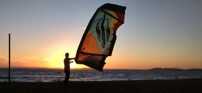 man with paraglider wing in front of sea at sunset