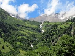 Mountains with a waterfall and green trees