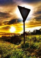 attention, traffic sign right of way in countryside at sunset