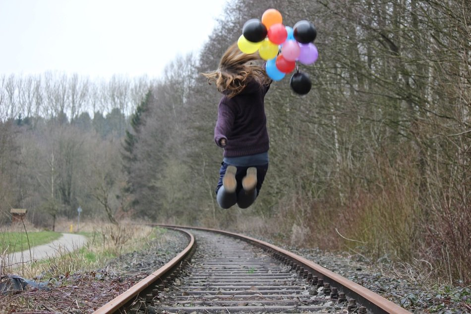 girl with balloons jumps on the train tracks