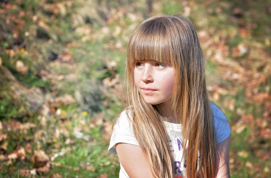 human child girl blond long hair in the forest