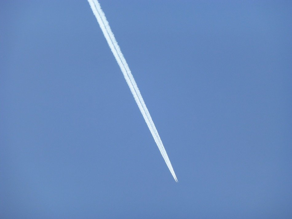 white plane trail in the blue sky