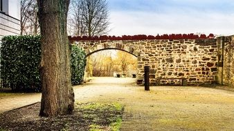 arched gateway in aged stone wall at fall, germany, kassel