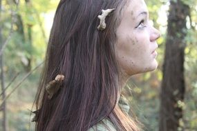 photo of a frightened young girl with dry leaves in her hair in a forest