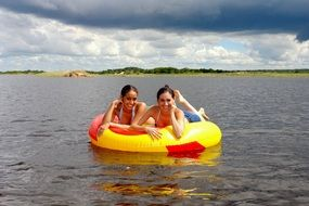 girls on an inflatable mattress on the water