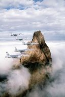 military planes flying at rock formation above clouds