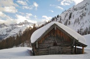 wooden hut in the snowy alps