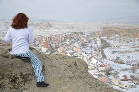 brunette sits on top of a mountain in Ð¡appadocia