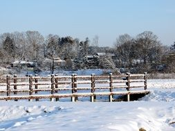 snowy winter in countryside, landscape with wooden bridge