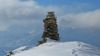 stone pile at snowy mountain landscape