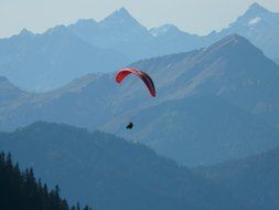 paraglider over the mountains in a blue haze