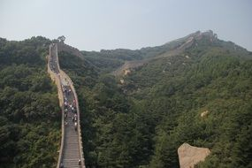 people walking on top of the great wall in mountain landscape, china