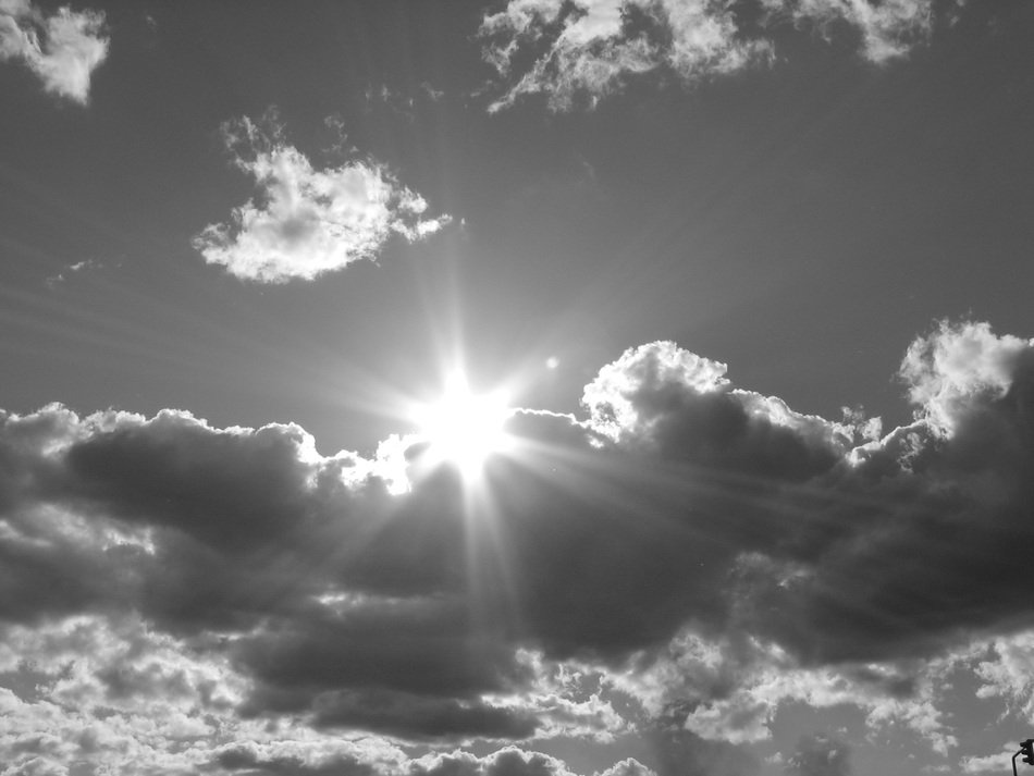 Black and white photo of bright Sun behind the clouds
