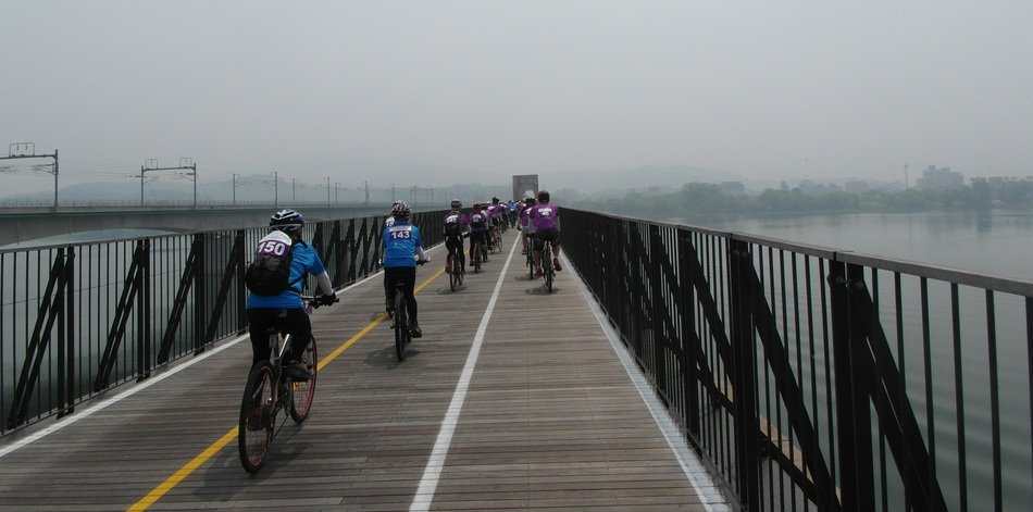 people cycling on bridge above water, south korea