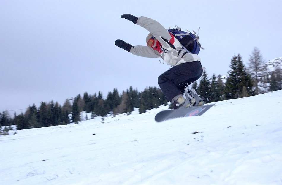 snowboarder jumping on a snowy slope