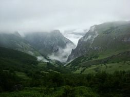 clouds above picturesque green mountain valley, spain, asturia, peak urriellu