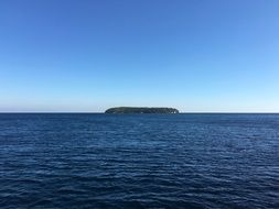 distant green island in blue sea