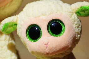 plush sheep with green eyes