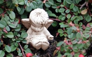 sculpture of a little angel in a green plant