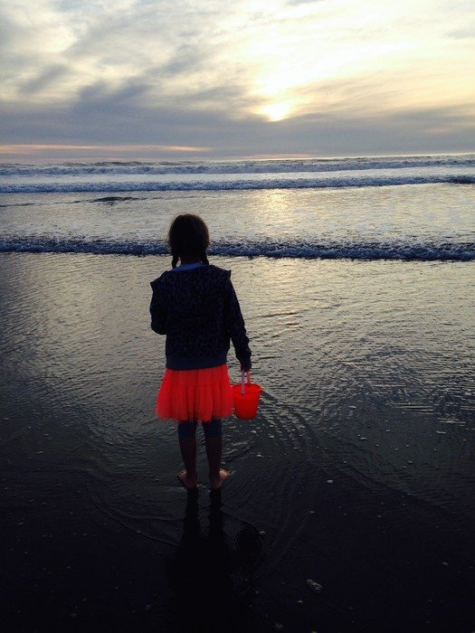 girl looks at the waves of the Pacific Ocean
