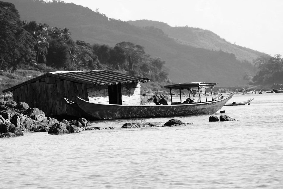 black and white photo of a hut and a fishing boat