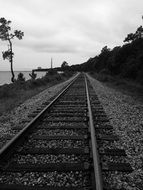 rails along the beach in black and white image