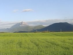 green field in front of scenic mountains, spain, santa cilia