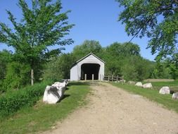 soil road to covered bridge in countryside, usa, massachusetts