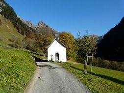 white chapel at road on green mountain side, germany, allgäu
