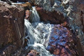 waterfall among colorful rocks