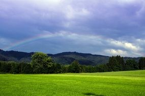 beautiful meadow and rainbow at clouds above distant mountains, landscape