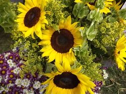 a huge bouquet of flowers such as sunflowers and daisies