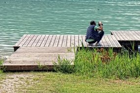 photographer on a wooden bridge near the water