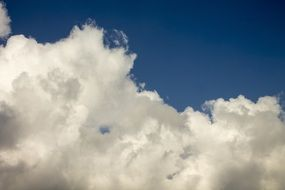 white cumulus clouds at deep blue sky