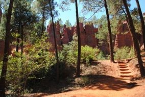 rocks of Red Ochre Natural Mineral Pigment in forest, france, roussillon