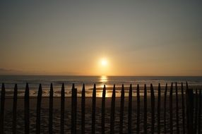 fence on the beach during sunset