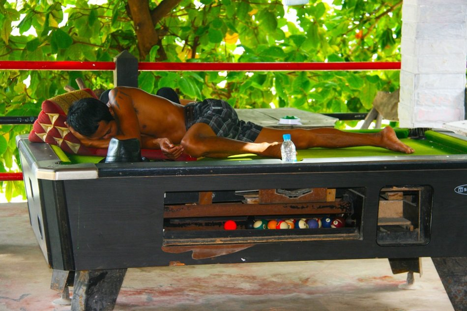 man sleeping on a pool table in Thailand