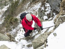 climber in a red jacket climbs the Alpine mountain