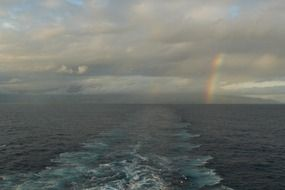 rainbow between clouds above sea