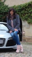 woman in jeans sittin on audi car