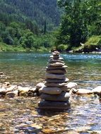 stone tower on a river in a mountain valley