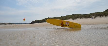 yellow surf board at water, uk, cornwall, porthkidney beach