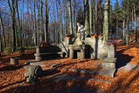 topless woman in crown, stone sculpture in forest at fall
