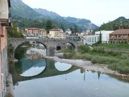 reflection of a stone bridge in a river in Italy