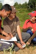 asian agriculture students measuring temperature of soil on field