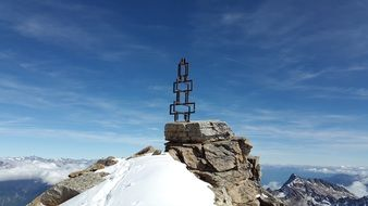 metal cross on top of a mountain under the sky