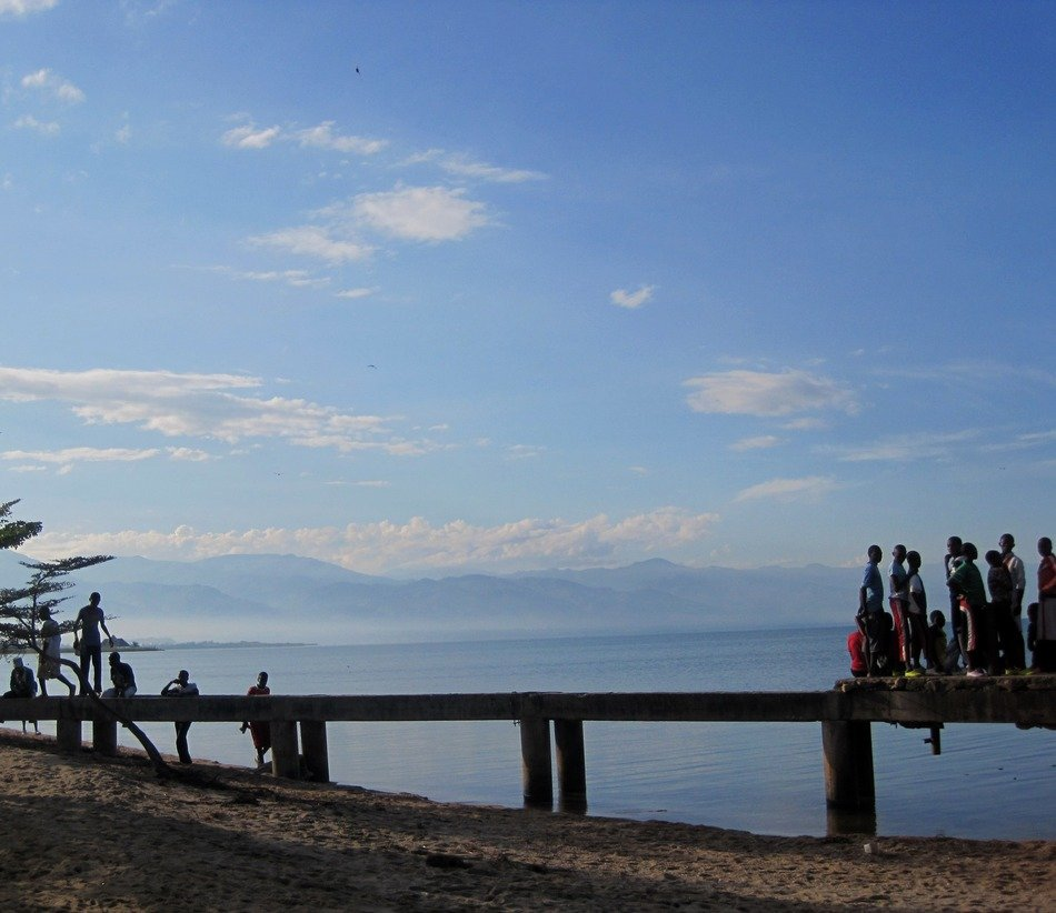 local people on pier at seashore in view of distant mountain range, africa