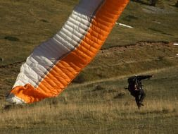 a man with a paraglider on the ground