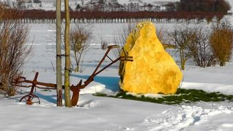 iron plow and yellow kament on a winter field in the countryside