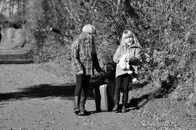 black and white photo two girls with luggage